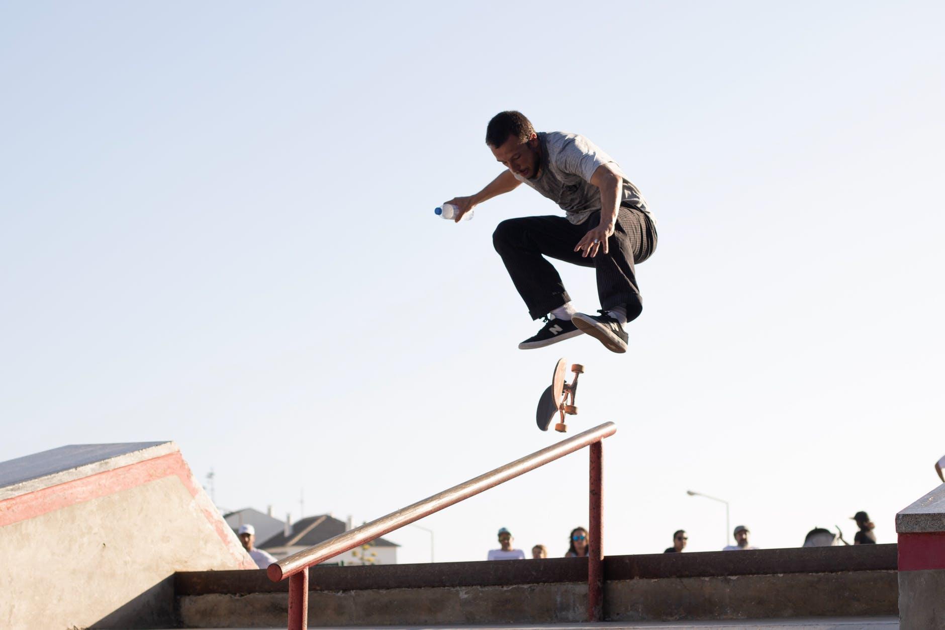 man wearing white t shirt performing skateboard tricks on rail under blue sky