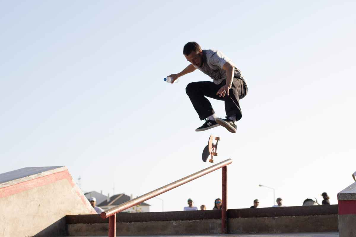 man wearing white t shirt performing skateboard tricks on rail under blue sky
