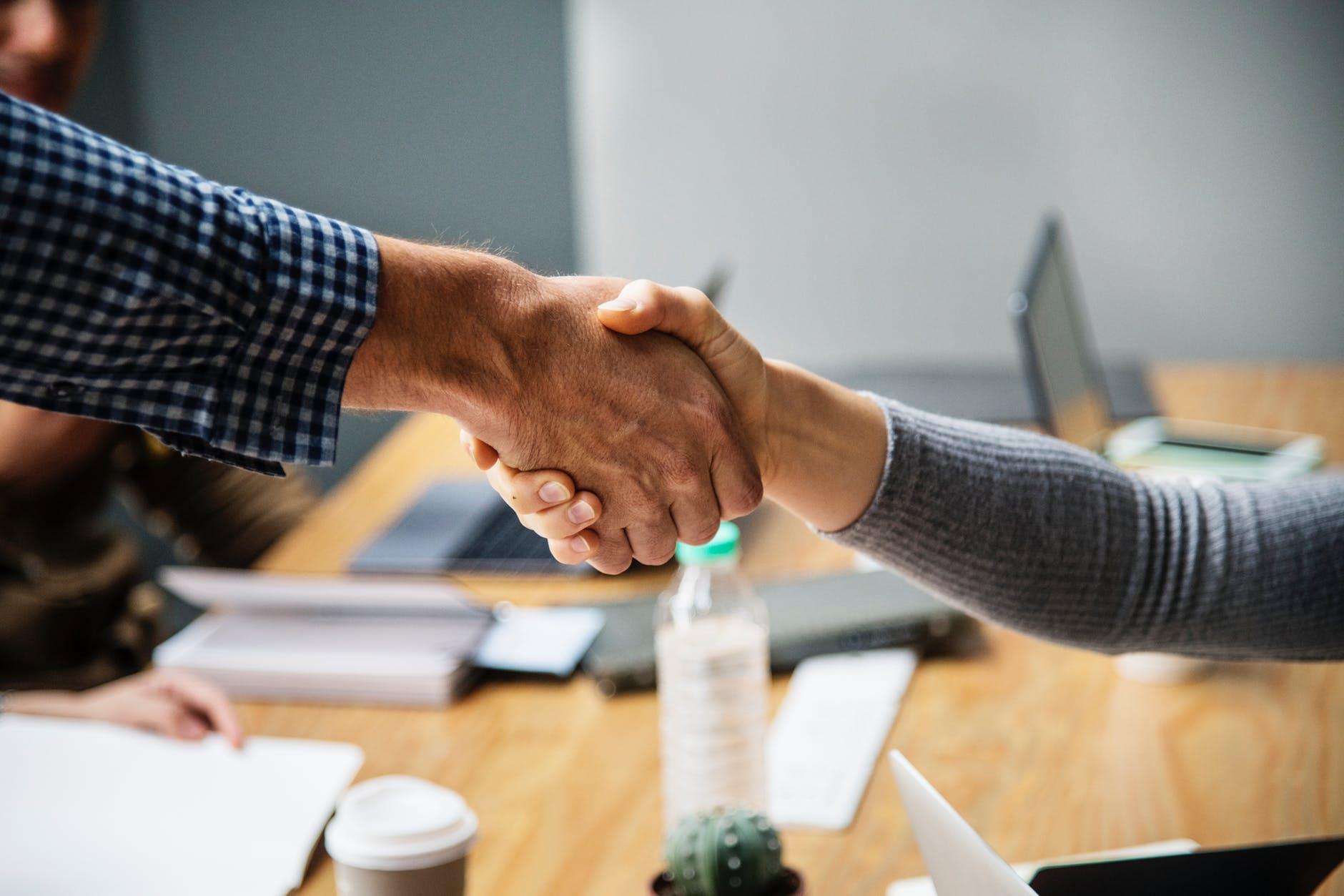 two person doing handshake beside table inside room